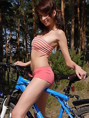 Playful girl starts getting undressed right on her bicycle and shows everything what she got.